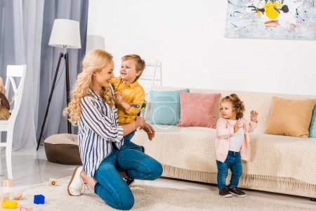 beautiful happy mother and beautiful little kids playing together at home