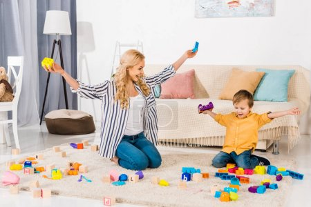 happy mother and son playing with colorful blocks at home