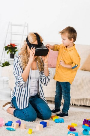 cute little son looking at mother using virtual reality headset at home
