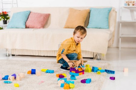 Photo for Adorable little boy playing with toy airplane and colorful blocks at home - Royalty Free Image