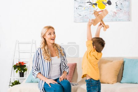 cheerful mother looking at cute little son playing with toy plane at home