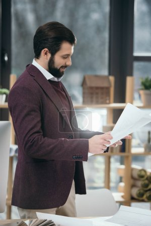 handsome architect working with blueprints in modern office