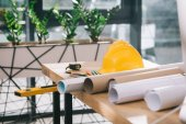 hardhat, tape measure and blueprints on table in modern architect office