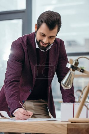 handsome architect working with blueprint in modern office