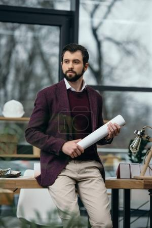 thoughtful architect holding blueprint in modern office