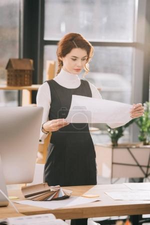 Photo pour Femme architecte travaillant avec plans sur lieu de travail au bureau - image libre de droit