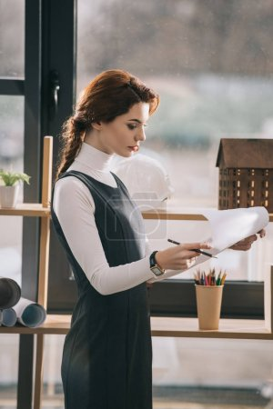 female architect working with blueprints at window in office