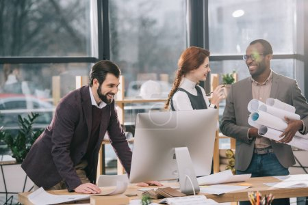 Photo pour Architectes multiethniques souriants travaillant avec plans et ordinateur de bureau moderne - image libre de droit