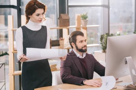 two architects working with blueprints and computer in modern office