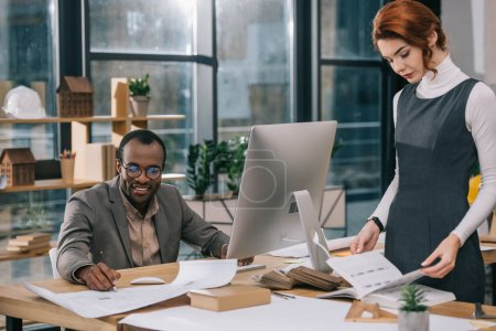 Photo for Multiethnic architects working with blueprints and computer in modern office - Royalty Free Image