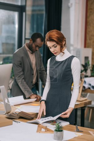female architect working in office, african american colleague behind