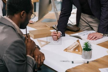 cropped view of multiethnic architects discussing and drawing blueprints in modern office