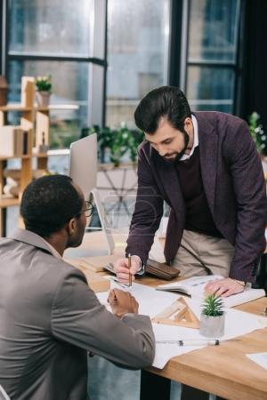 Photo pour Architectes multiethniques discutant et dessin des plans au bureau moderne - image libre de droit