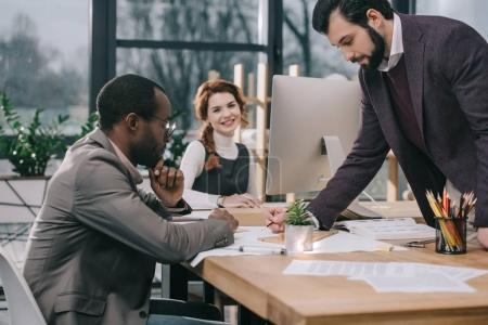 multiethnic architects discussing building plans in office