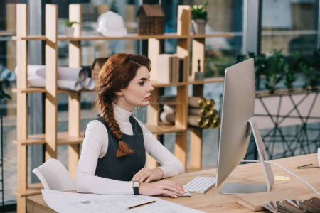female architect working with computer and blueprint in modern office