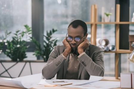 thoughtful african american architect looking at blueprints in office