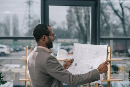 male african american architect looking at building plan in modern office