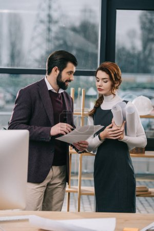 two architects discussing documents and blueprints in office
