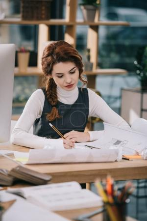 Photo for Female architect drawing blueprints with pencil and compasses - Royalty Free Image