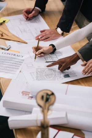 Foto de Recortada visión de arquitectos multiétnicos discusión de documentos y elaboración de planos en oficina - Imagen libre de derechos