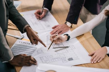 Photo for Cropped view of multiethnic architects discussing and working with blueprints and documents in office - Royalty Free Image