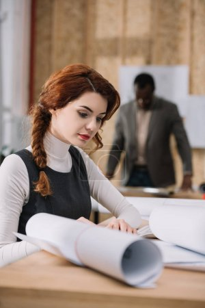 beautiful female architect discovering building plans while her colleague standing blurred on background