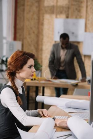 beautiful female architect using computer while her colleague standing blurred on background