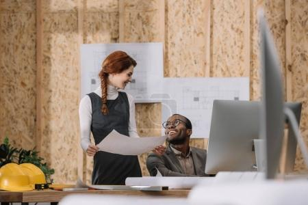 young architects discussing building plan while working at office