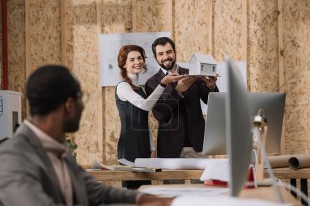 Foto de Jóvenes arquitectos que muestra el modelo de casa a su colega mientras él trabaja con la computadora - Imagen libre de derechos