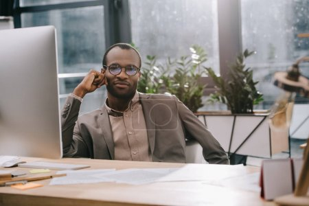 handsome african american businessman sitting at workplace and looking at camera