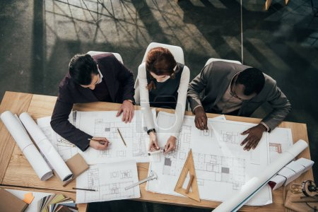 Photo for High angle view of team of architects working together with plans at office - Royalty Free Image