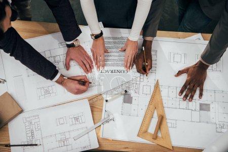 Photo pour Recadrée tir de l'équipe d'architectes avec contrat et les plans de construction - image libre de droit