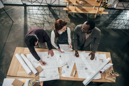 high angle view of team of architects working with building plans at office