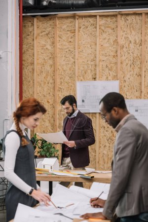 team of architects working together at modern office with plywood decor