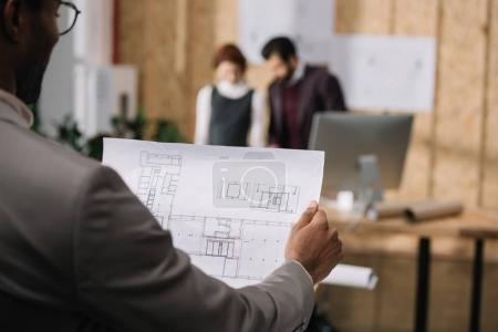 cropped shot of architect discovering plan with blurred colleagues working on background