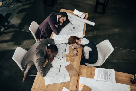 high angle view of overworked team of architects sleeping at office