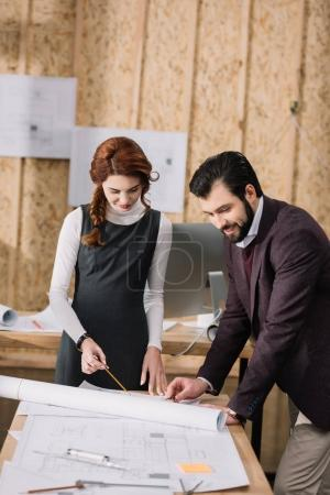young architects discussing architectural plans at modern office