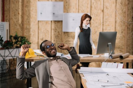 handscome african american architect stretching in chair while his colleague working with computer