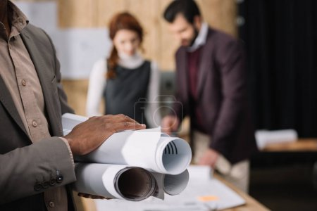 cropped shot of architect holding rolled plans with blurred colleagues working on background