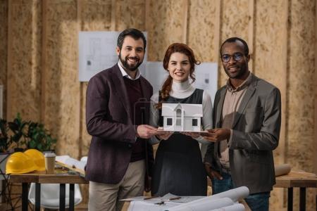 Foto de Feliz equipo de arquitectos con modelo en miniatura del edificio en la oficina - Imagen libre de derechos