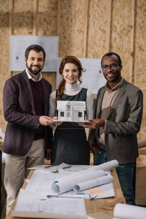 young multiethnic team of architects holding miniature model of building