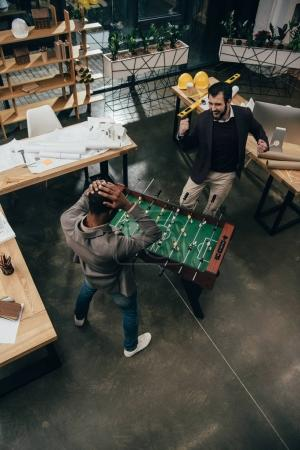 high angle view of young architects playing table football in office