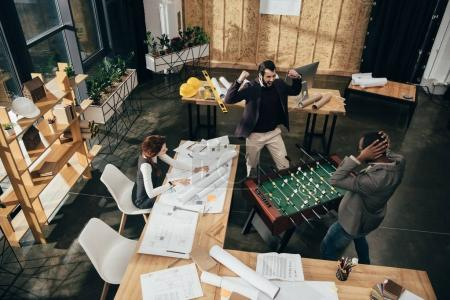 high angle view of young architects playing table football at modern office
