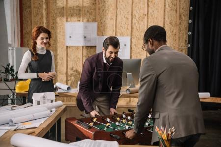 architects playing table football at modern office