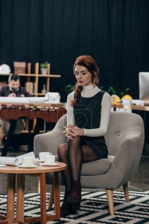 Photo for Young beautiful businesswoman sitting on armchair and looking at papers on table - Royalty Free Image