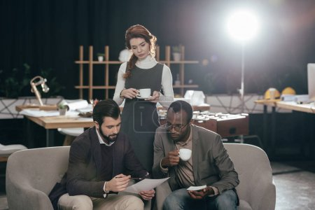 young multiethnic businesspeople working together and drinking coffee