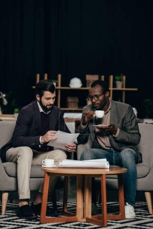 multiethnic young businessmen sitting in armchairs with coffee and discussing documents