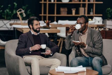 Photo pour Hommes d'affaires réussis assis dans un fauteuil avec du café - image libre de droit