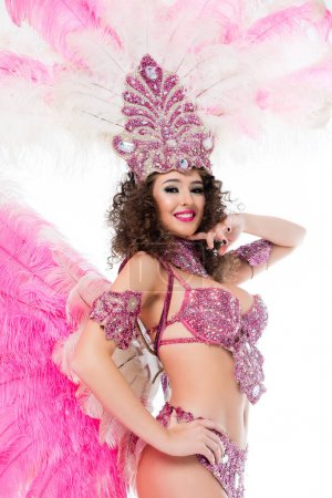 smiling woman posing in carnival costume with pink feathers and gems, isolated on white