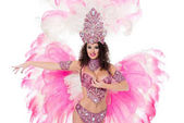 attractive woman dancing in traditional carnival costume with pink feathers, isolated on white